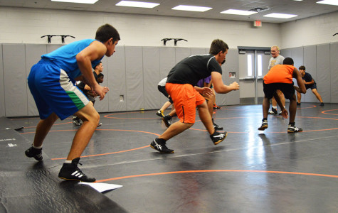 During practice, the boys wresting team goes through extensive warm-ups, preparing themselves for a competitive season.