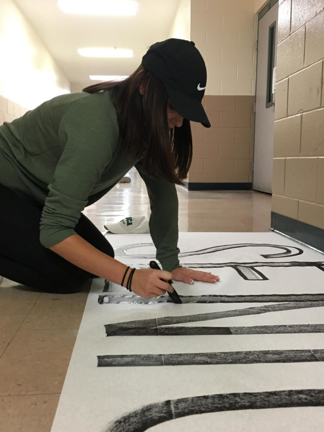 A leadership member works on a banner for the Pink-Out pep rally.